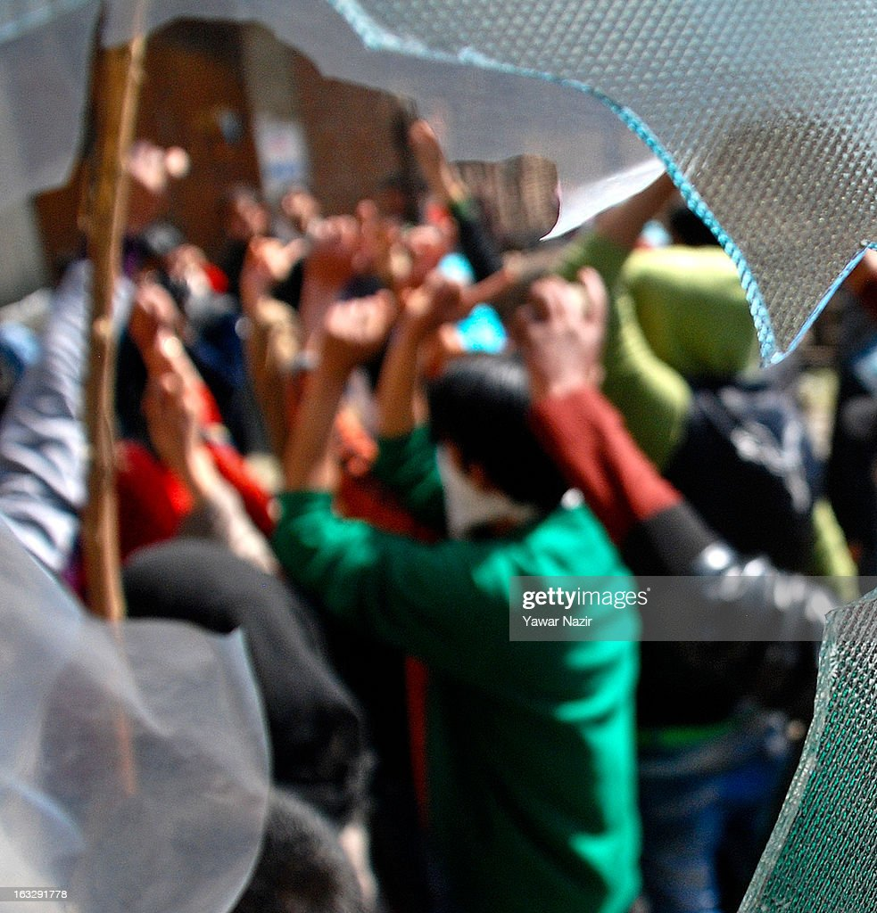 Kashmiri Muslims shout anti-Indian and pro-freedom slogans after the window panes of their residential houses were broken by Indian military forces during a curfew-like restriction on March 7, 2013 in Srinagar, the summer capital of Indian Administered Kashmir, India. Clashes erupted in most parts of Kashmir today leaving scores of people injured. Meanwhile Indian authorities imposed curfew-like restrictions for the second consecutive day in most parts of Kashmir following the killing of a Kashmiri youth by the Indian army in North Kashmir's Baramulla district.