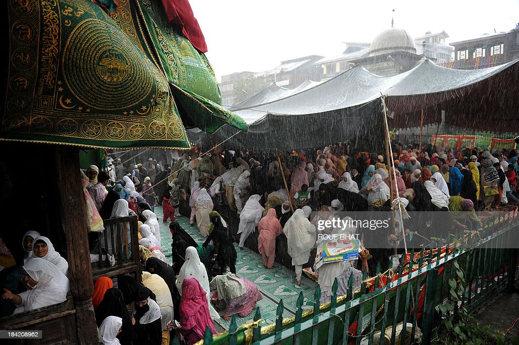 Kashmiri Muslims take shelter during a heavy rainfall in front of the 600-year-old shrine of Syed Mir Ali Hamdani, during the annual Urs in downtown Srinagar on October 12, 2013. The revered Persian preacher Hamdani is credited with introducing Islam in Kashmir during the 13th centuray AD besides greatly influencing the region's culture and economy. Kashmiri Muslims throng the shrine every year during the Urs. AFP PHOTO/Rouf BHAT