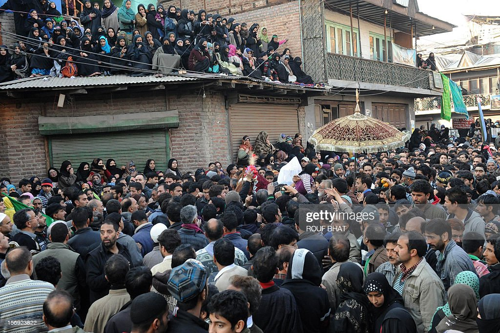 Kashmiri muslims touch the face of a horse symbolising the horse of Imam Hussein during a religious procession on the tenth day of Ashura in Srinagar on November 25, 2012. During the Shiite Muslim holy month of Moharram, large processions are formed and the devotees parade the streets holding banners and carrying models of the mausoleum of Hazrat Imam Hussain and his people, who fell at Karbala. Shias show their grief and sorrow by inflicting wounds on their own bodies with sharp metal tied to chains to depict the sufferings of the martyrs. AFP PHOTO/ Rouf BHAT