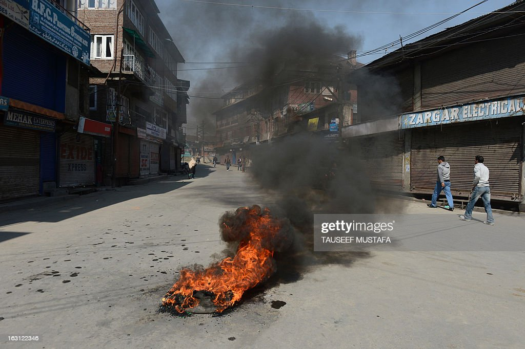 Kashmiri Muslims walk past burning tyres during a spontaneous strike to protest the death of 28 year old Kashmiri student, Mudassir Qamran Malla in the Indian city of Hyderabad at the weekend, in Srinagar on March 5, 2013. The Kashmiri student was buried in his native village in the Pulwama district on Monday with the family rejecting the police claim that he had commited suicide. AFP PHOTO/Tauseef MUSTAFA