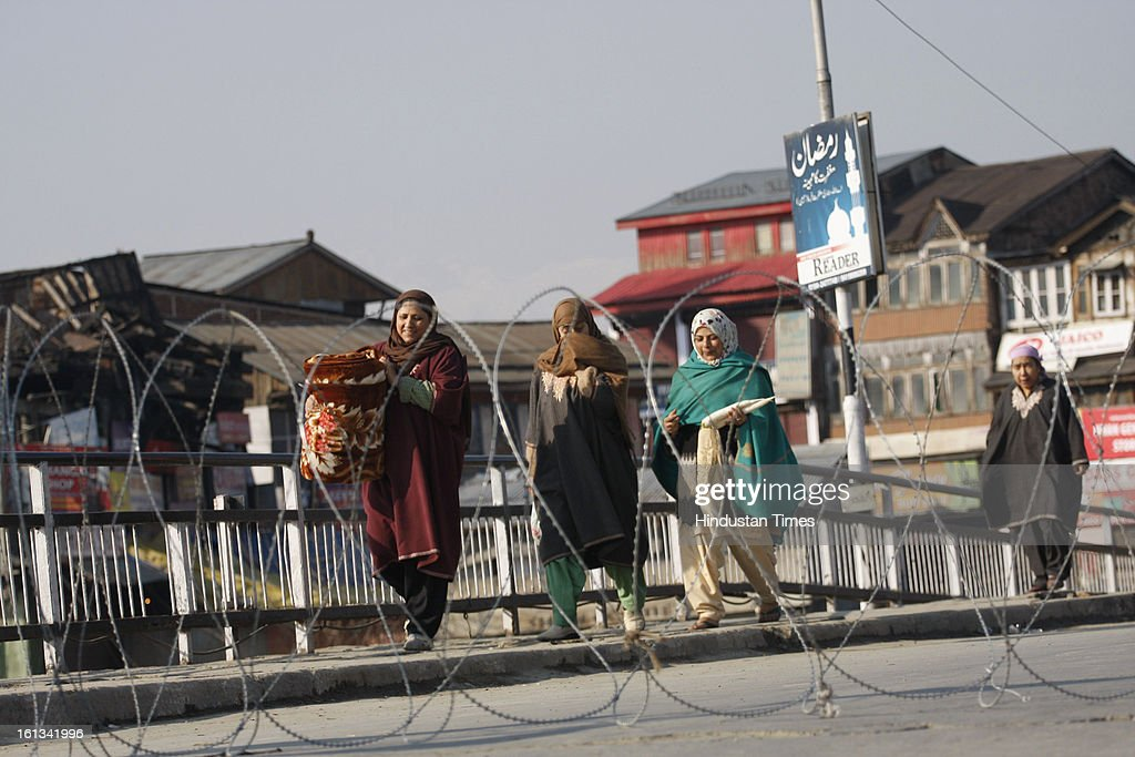 Kashmiri pedestrians are walking on deserted street after the parliament attack convict, Muhammad Afzal Guru was hanged in New Delhi, during Second day curfew on February 10, 2013 in Srinagar, India. Guru, who was found guilty of conspiring and sheltering the militants who attacked Parliament on December 13, 2001 in which nine people were killed, was buried in the prison premises as per the jail manual.