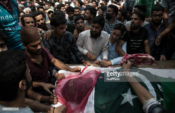 Kashmiri people get ready to offer prayers during the funeral of local rebel Adil Ahmed Saturday June 17 on the outskirts of Srinagar...