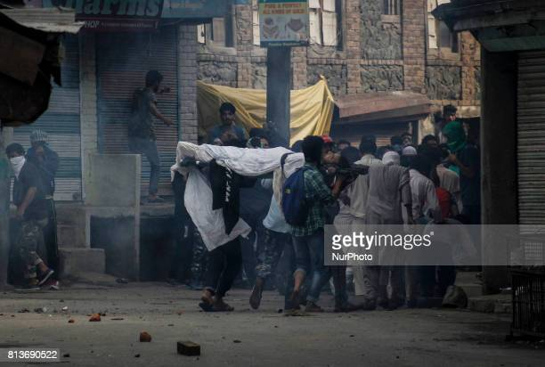 Kashmiri people run with the body of a local rebel Sajad Gilkar after it was tear gassed by Indian forces during his funeral Wednesday July 12 2017...