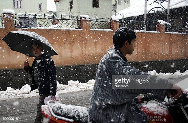 A kashmiri people walking during a fresh snow fall in Srinagar summer capital of indian controled kashmir on 11 march 2014 Kashmir has vitnased have...