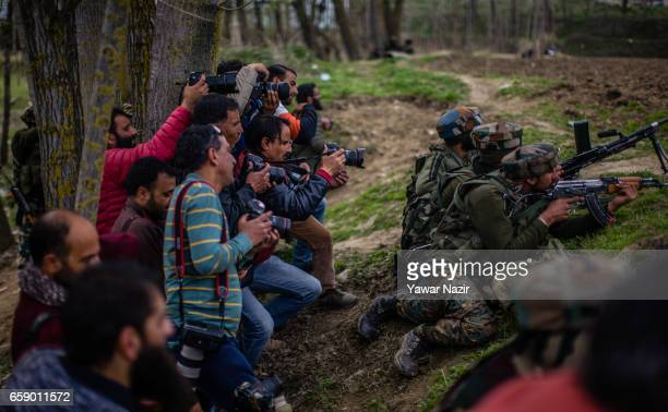 Kashmiri Photojournalists take pictures next to the Indian government forces during a heavy exchange of fire between suspected rebels and Indian...