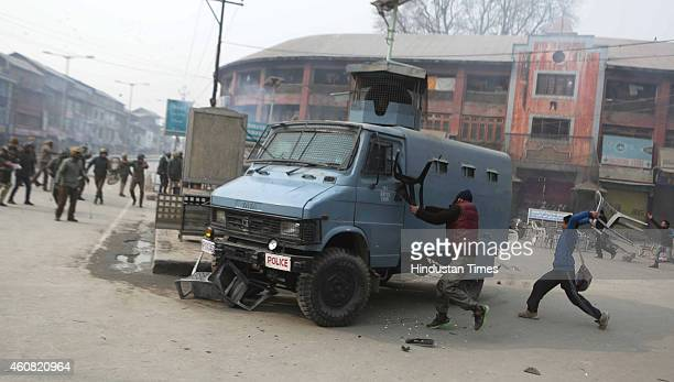 Kashmiri protester throw chair at paramilitary vehicle during a protest at Lal Chowk on December 24 2014 in Srinagar India Clashes erupted as JKLF...