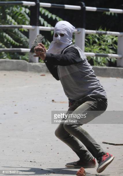 Kashmiri protester throws stone at police and paramilitary soldiers during curfew in Lal Chowk area on July 8 2017 in Srinagar India Authorities...