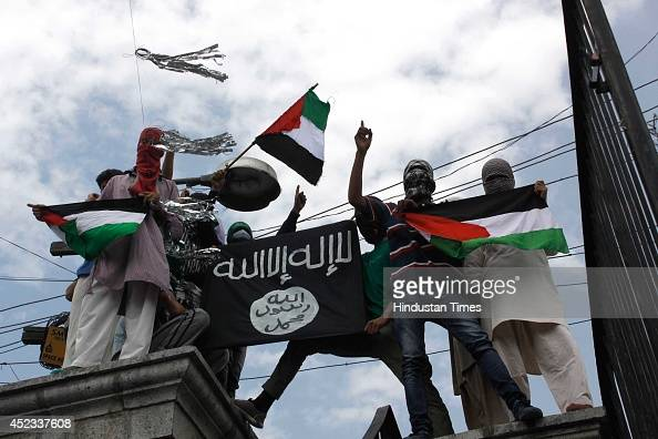 Kashmiri protesters hold up a flag of the Islamic State of Iraq and the Levant during a protest against Israeli military operations in Gaza on July...