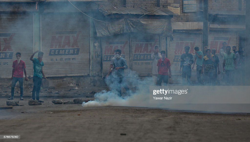 Kashmiri protesters shout anti Indian slogans in front the exploding the teargas after they defied curfew following violence that has left over 40...