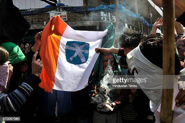 Kashmiri protesters shout AntiIndia slogan as they burn tricolour national flag during a protest against Tral killing and arrest of separatist leader...