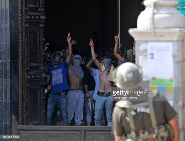Kashmiri protesters shout slogans as they stand near the entrance of Jamia Masjid or Grand mosque during a protest on August 11 2017 in Srinagar India