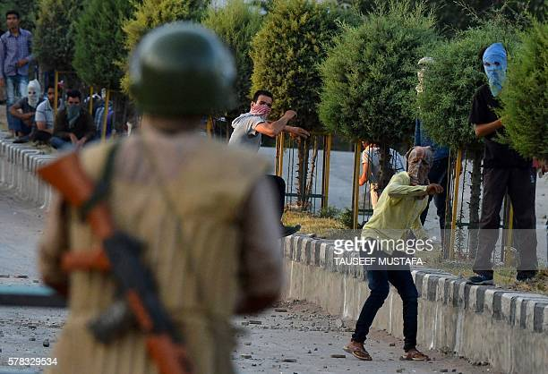TOPSHOT Kashmiri protesters throw stones after Indian paramilitary troops fired tear gas during clasesh in Srinagar on July 212016 Residents in...