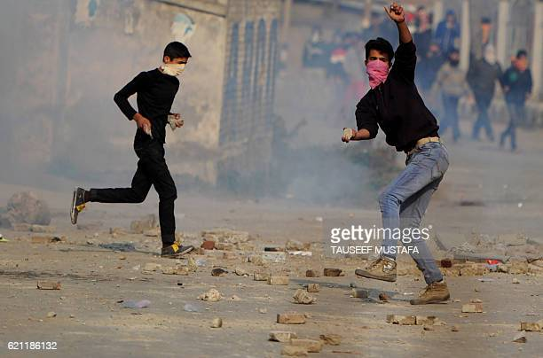 Kashmiri protesters throw stones during a clash with Indian police during the funeral procession for Qaiser Hamid in Srinagar on November 5 2016 The...