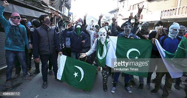 Kashmiri protestors hold Pakistani flags during a protest on November 27 2015 in Srinagar India Police fired dozens of tear smoke canisters and...