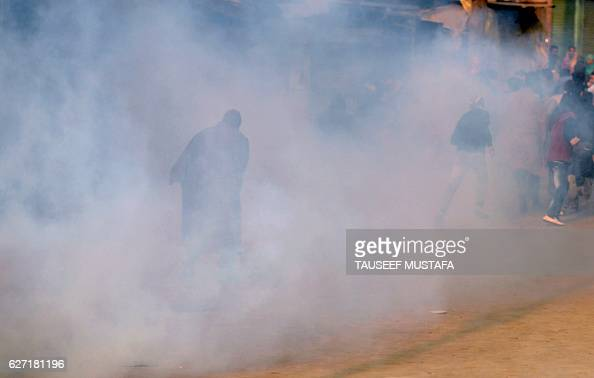 Kashmiri protestors run away after Indian police fired tear gas during a rally in downtown Srinagar on December 2 2016 Kashmir's chief priest and...