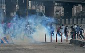Kashmiri protestors run away after Indian police fired tear gas to stop the crowd from marching towards Srinagar's downtown Lal Chowk area on July 26...