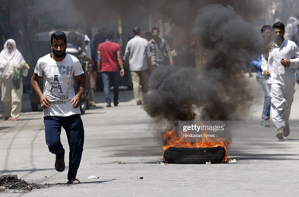 Kashmiri protestors run past a burning tire during a protest against killing of 4 people in BSF firing on July 18, 2013 in Srinagar, India. Four people were killed today when security personnel opened fire at a mob that had gathered at a BSF camp in Ramban district protesting against alleged manhandling of an Imam of the area by the force. Curfew would be imposed in Srinagar and all other major towns in the Kashmir Valley from Friday morning as a precautionary measure.