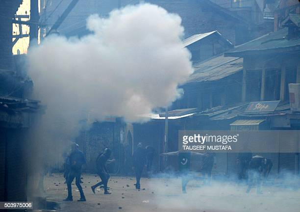 TOPSHOT Kashmiri protestors shout slogans as teargas smoke drifts across a road during clashes with Indian police officials in Srinagar on January 8...