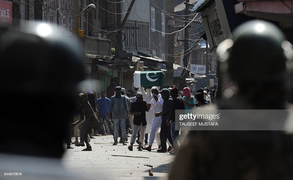 Kashmiri protestors shout slogans at Indian police personnel during a clash in Srinagar on July 1, 2016. Police fired teargas shells and rubber bullets to disperse Kashmiris protesting against Indian rule after the last Friday prayers of Ramadan near the main Jamia Masjid mosque. Several rebel groups have for decades been fighting Indian forces deployed in the region, seeking independence or a merger of the territory with Pakistan. / AFP / TAUSEEF