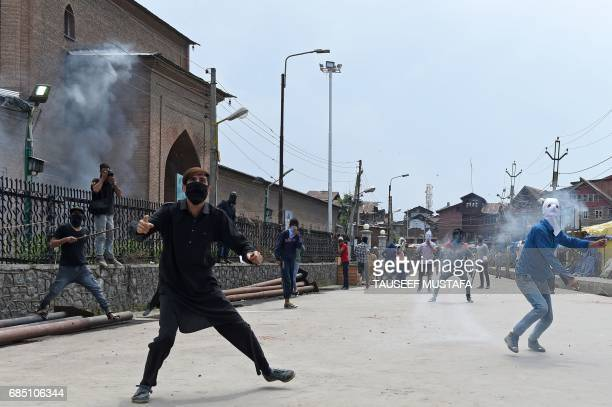 TOPSHOT Kashmiri protestors throw stones towards Indian government forces during clashes after Friday congregational prayers outside The Jamia Masjid...