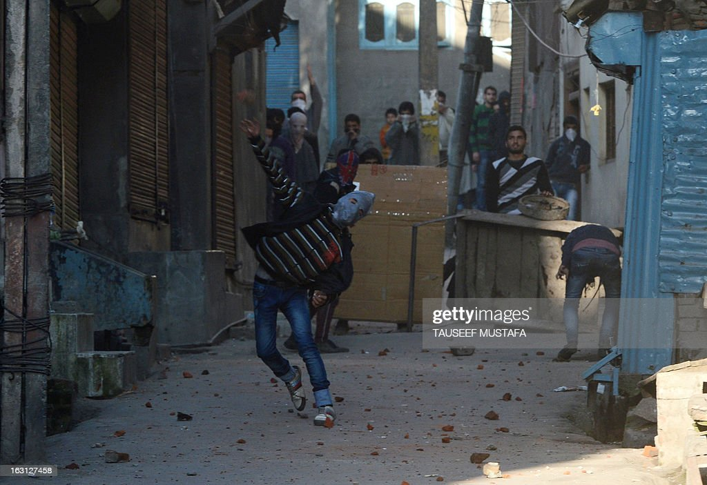 Kashmiri protestors throw stones towards Indian police during a spontaneous strike to protest the death of 28-year old Kashmiri student, Mudassir Qamran Malla in the Indian city of Hyderabad over the weekend, in Srinagar on March 5, 2013. The Kashmiri student was buried in his native village in the Pulwama district on Monday with the family rejecting the police claim that he had commited suicide. AFP PHOTO/Tauseef MUSTAFA