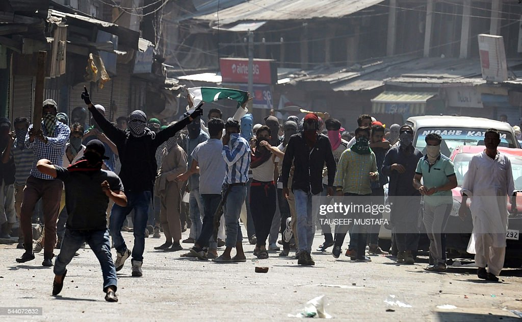 Kashmiri protestors throw stones towards Indian police personnel during a clash in Srinagar on July 1, 2016. Police fired teargas shells and rubber bullets to disperse Kashmiris protesting against Indian rule after the last Friday prayers of Ramadan near the main Jamia Masjid mosque. Several rebel groups have for decades been fighting Indian forces deployed in the region, seeking independence or a merger of the territory with Pakistan. / AFP / TAUSEEF
