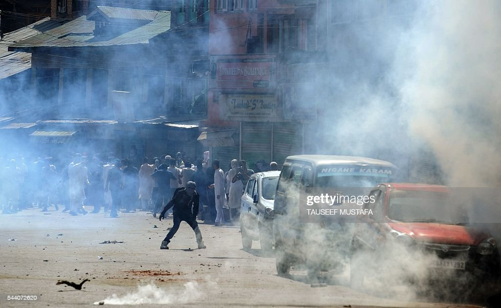 Kashmiri protestors throw stones towards Indian police personnel through teargas smoke clouds during a clash in Srinagar on July 1, 2016. Police fired teargas shells and rubber bullets to disperse Kashmiris protesting against Indian rule after the last Friday prayers of Ramadan near the main Jamia Masjid mosque. Several rebel groups have for decades been fighting Indian forces deployed in the region, seeking independence or a merger of the territory with Pakistan. / AFP / TAUSEEF