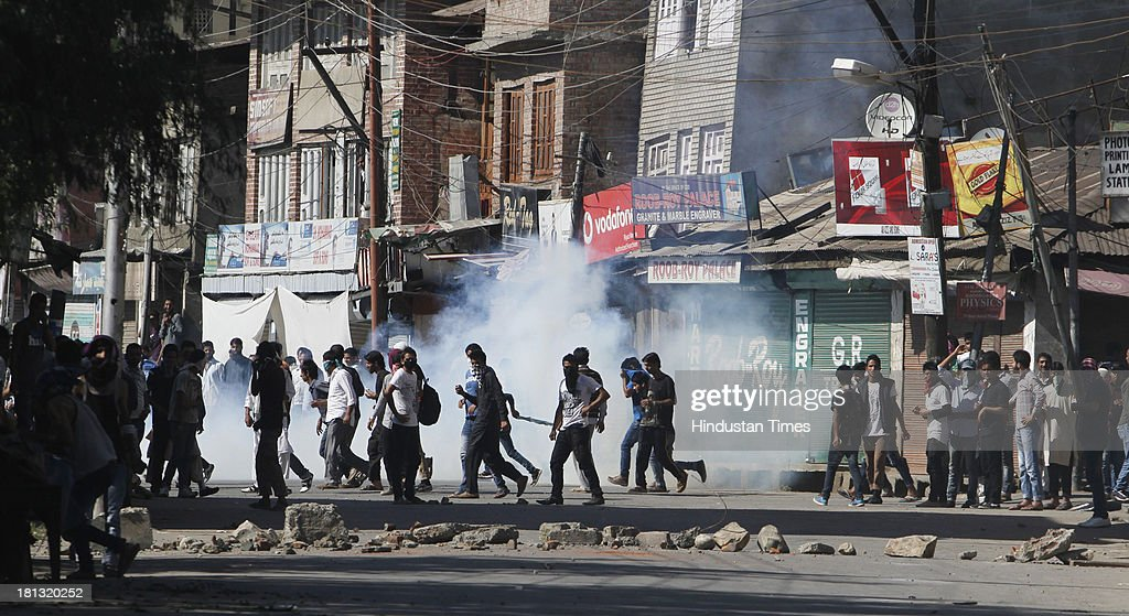 Kashmiri protestors throwing stones on CRPF during clash on September 20, 2013 in Srinagar, India. Police fired dozens of tear smoke shells and pellets to disperse hundreds of youth who clashed with them after Friday afternoon congregational prayers in Srinagar. The youth were protesting the civilian killings and continuous curfew in Shopian town, 50 Km south of Srinagar