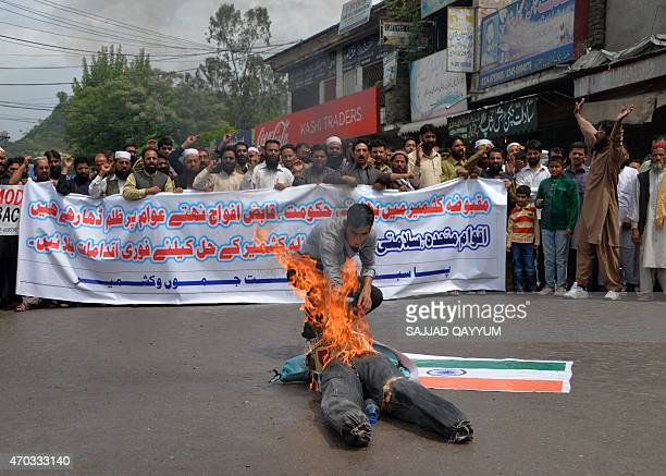 A Kashmiri refugee from Indianadministered Kashmir burns an effigy of Indian Prime Minister Narendra Modi as activists from the 'PasbaneHurriyat'...
