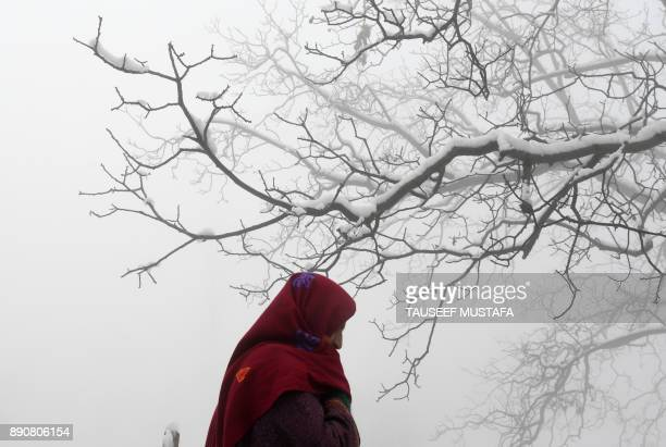A Kashmiri resident walks along a road following fresh snowfall on the outskirts of Srinagar on December 12 2017 / AFP PHOTO / Tauseef MUSTAFA