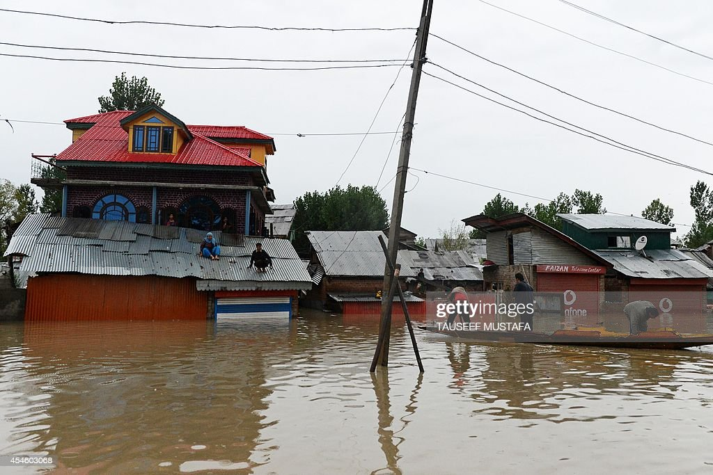 Kashmiri residents are pictured on the roof of a house as a raft approaches to assist during floods in the outskirts of Srinagar on September 4 2014...
