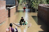 Kashmiri residents cross a flooded neighbourhood by makeshift raft in Srinagar on September 11 2014 The floods and landslides from days of heavy...