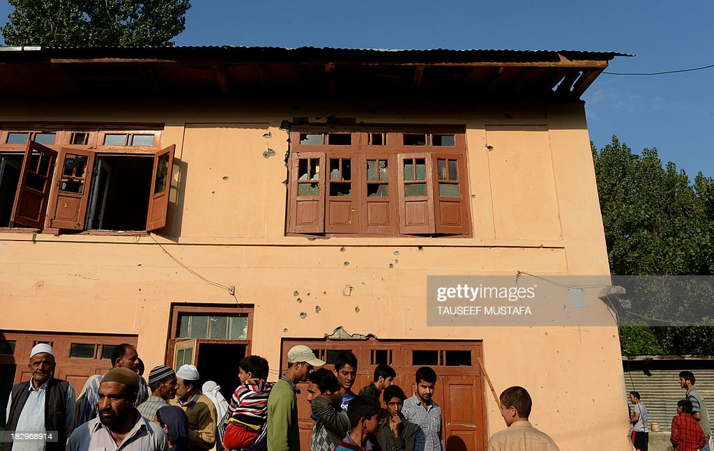 Kashmiri residents gather outside a damaged house after a gun battle on the outskirts of Srinagar on October 3, 2013, following an encounter with suspected militants in the restive state. Four policemen were injured in a late-night encounter on the outskirts of Srinagar, as suspected militants who were hiding inside a house escaped under the cover of darkness police officials said. AFP PHOTO/Tauseef MUSTAFA