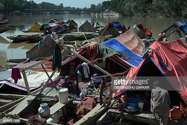 Kashmiri residents look on as they sit on the boats where they have taken temporary shelter following flooding in Pulwama some 45 kms south of...