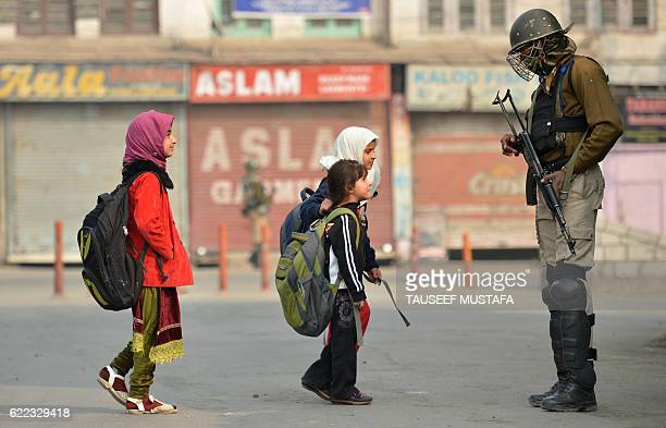 TOPSHOT Kashmiri residents walk past Indian paramilitary troopers as they stand guard during curfew and restrictions in downtown Srinagar as the...