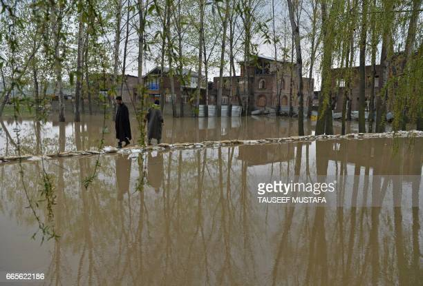 TOPSHOT Kashmiri residents walk through floodwater on the outskirts of Srinagar on April 7 2017 Three soldiers have died after avalanches struck a...