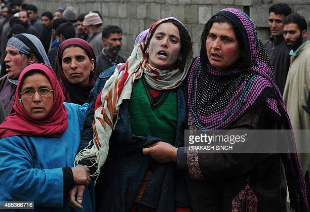 Kashmiri residents weep as they try to comfort Zareena Shafi wife of Special Police Officer Mohammed Shafi during his funeral procession in Chenabal...