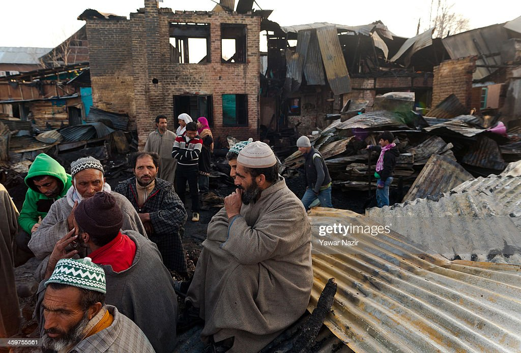 Kashmiri rest on the debris of their houses after a fire gutted many residential houses on December 30, 2012, in Srinagar, the summer capital of Indian administered Kashmir, India. Many families were left homeless amid sub-zero temperatures during the harshest 40-day period (Chilay Kalan) of the winter, after at least 30 residential houses were damaged in a devastating fire on the bank of famous Dal Lake near the Hazratbal shrine, in the outskirts of the Srinagar. The incident engulfed the area during the preceding night, an official said. No injuries were reported.