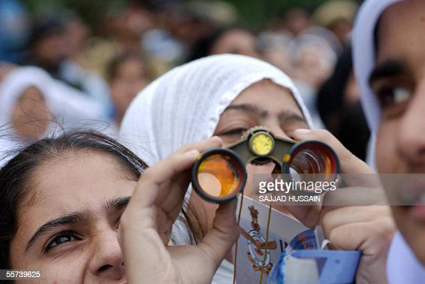 Kashmiri school children use binoculars as they watch pilots from the Indian Air Force Suryakiran Formation Aerobatic Team show off their skills...