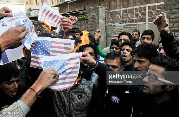 Kashmiri Shia Muslims burning flags of America and Israel during a protest on December 18 2015 in Srinagar India The Shia Muslims were protesting...