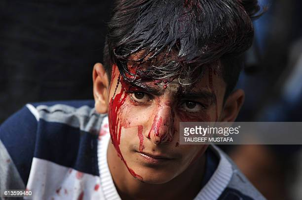A Kashmiri shiite muslim mourner pauses during selfflagellation in a procession on the seventh day of Muharram in downtown Srinagar on October 9 2016...