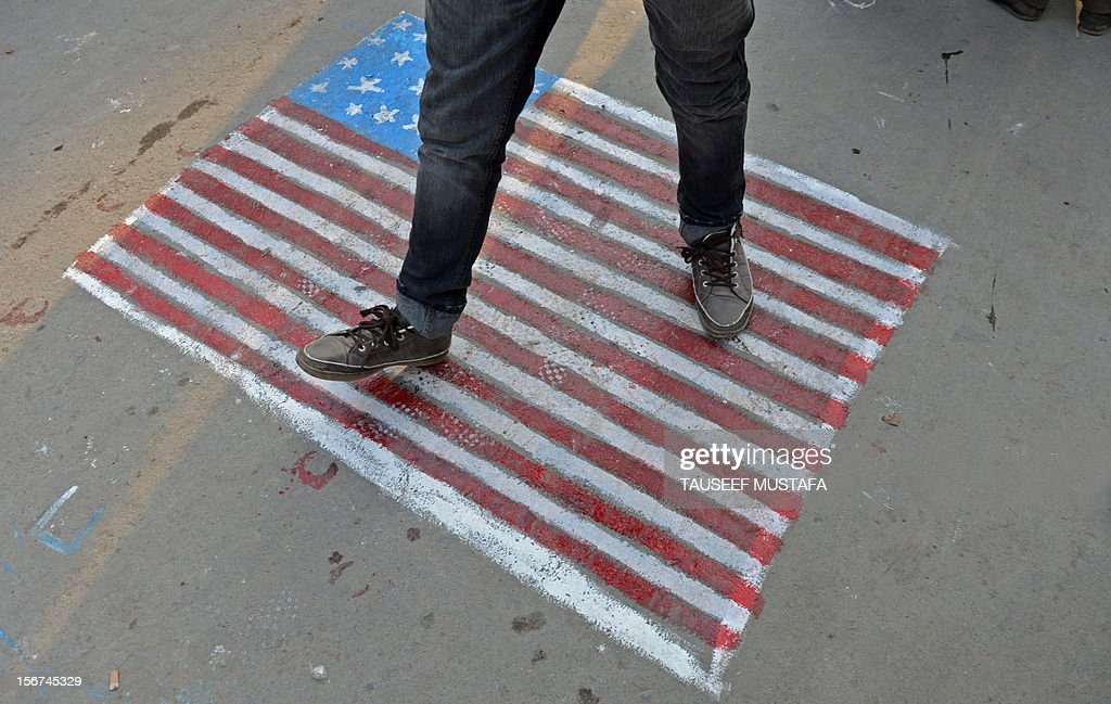 A Kashmiri Shiite Muslim steps on a US flag painted on the street during a religious procession held on the fourth day of Ashura, which remembers the slaying of the Prophet Mohammed's grandson in southern Iraq in the seventh century, in Srinagar on November 20,2012. During the Shiite Muslim holy month of Muharram, large processions are formed and the devotees parade the streets holding banners and carrying models of the mausoleum of Hazrat Imam Hussain and his people, who fell at Karbala. Shias show their grief and sorrow by inflicting wounds on their own bodies with sharp metal tied to chain to depict the sufferings of the martyrs. AFP PHOTO/ Tauseef MUSTAFA