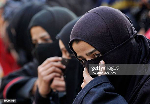 Kashmiri Shiite Muslim women and girls watch a religious procession in downtown Srinagar on December 62011 held on the 10th day of Ashura which...