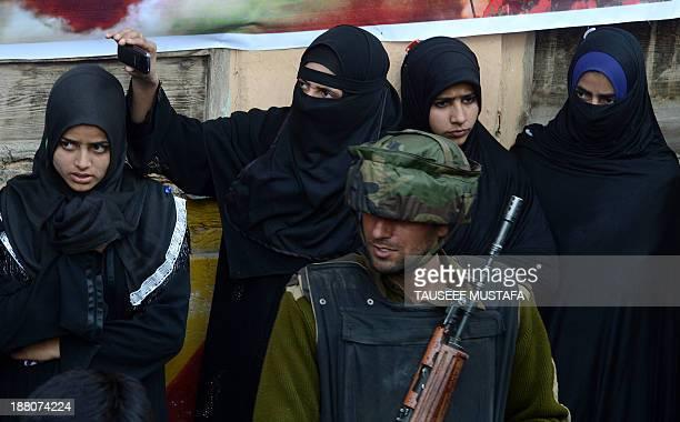 Kashmiri Shiite Muslim women look on during a religious procession marking Ashura in Srinagar on November 15 2013 Ashura mourns the death of Imam...