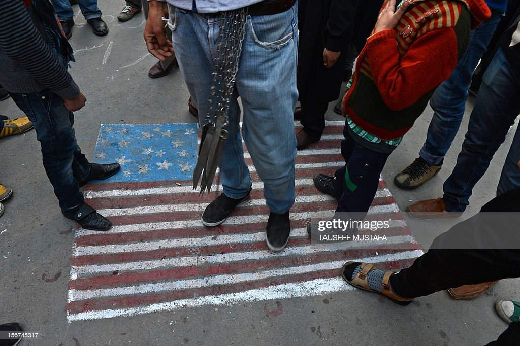 Kashmiri Shiite Muslims step on a US flag painted on the street during a religious procession held on the fourth day of Ashura, which remembers the slaying of the Prophet Mohammed's grandson in southern Iraq in the seventh century, in Srinagar on November 20,2012. During the Shiite Muslim holy month of Muharram, large processions are formed and the devotees parade the streets holding banners and carrying models of the mausoleum of Hazrat Imam Hussain and his people, who fell at Karbala. Shias show their grief and sorrow by inflicting wounds on their own bodies with sharp metal tied to chain to depict the sufferings of the martyrs. AFP PHOTO/ Tauseef MUSTAFA