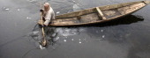 Kashmiri shikarawalla breaking the ice on frozen Dal Lake on January 2 2014 in Srinagar India A cold wave further tightened its grip in Jammu and...