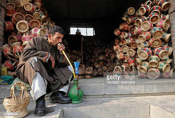 A Kashmiri shopkeeper smokes a hookah while selling 'Kangir' traditional Kashmiri fire pots in Srinagar on December 8 2010 With the arrival of winter...