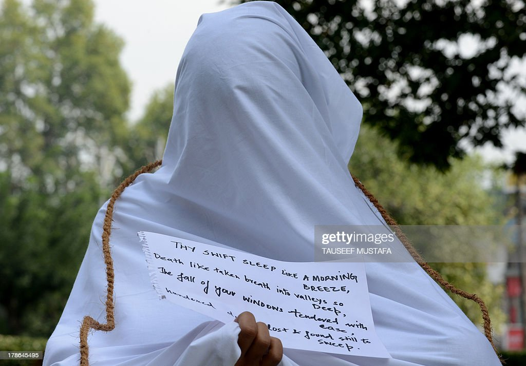 A Kashmiri student, seen covered in a shroud while holding a note, joins activists from the Association of Parents of Dissapeared people (APDP) during a protest on the International Day of the Disappeared in Srinagar on August 30, 2013. The APDP is demanding the setting up of a commission to probe the disappearances of people in Kashmir since 1989. An armed insurgency against Indian rule in Kashmir has claimed 47,000 lives since 1989 with separatists putting the toll twice as high. AFP PHOTO/Tauseef MUSTAFA