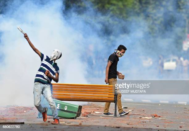 A Kashmiri student throws a teargas canister back towards Indian security personnel during in central Srinagar's Lal Chowk on May 9 2017 Police fired...