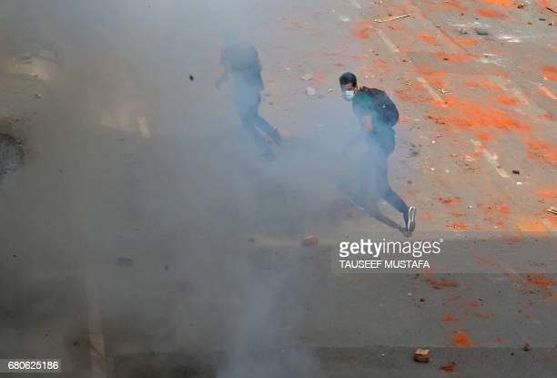 Kashmiri students run after Indian police fired tear smoke shells during clashes with Indian government forces in central Srinagar's Lal Chowk on May...